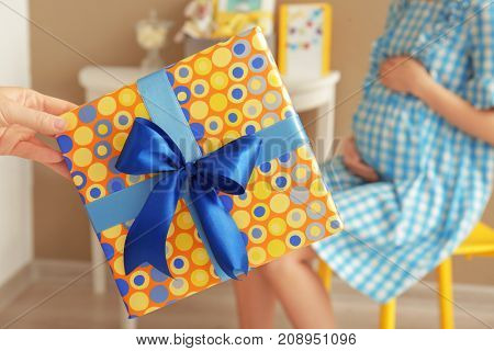 Hand holding baby shower gift and blurred pregnant woman indoors