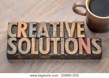 creative solutions word abstract in vintage letterpress wood type with a cup of coffee