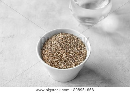 Bowl with chia seeds and glass of water on table