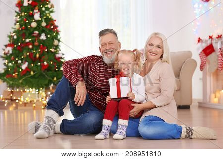Happy senior couple with granddaughter and Christmas gift at home
