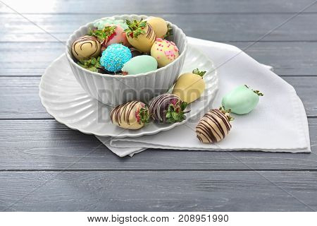 Bowl with tasty chocolate dipped and glazed strawberries on wooden table