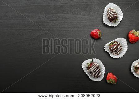 Tasty chocolate dipped strawberries on dark table