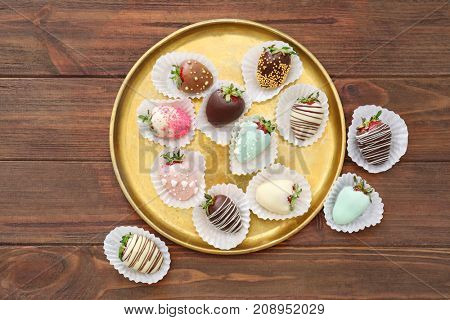 Plate with tasty glazed and chocolate dipped strawberries on wooden table
