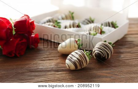 Box with tasty chocolate dipped strawberries on table