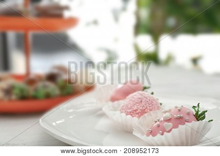 Plate with tasty glazed strawberries on table
