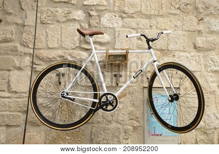 BESALU, SPAIN - JULY 26, 2017: White bike on stone wall in Besalu a medieval town of Girona Catalonia Spain.