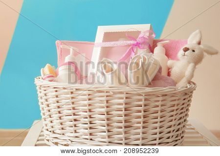 Wicker basket with baby shower gifts on table