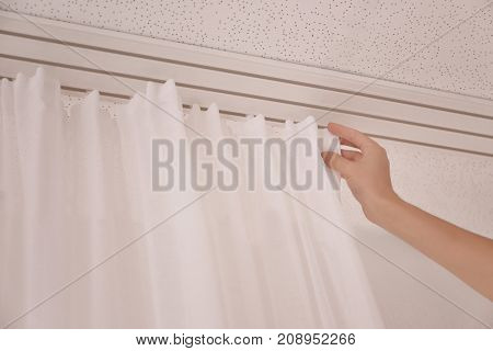 Woman hanging beautiful white curtains indoors, closeup