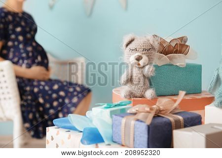 Gifts for baby shower and blurred pregnant woman indoors