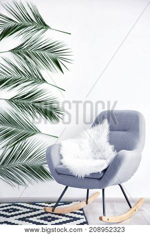 Stylish interior of room decorated with tropical leaves