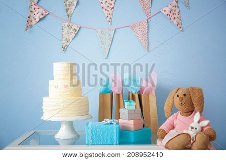 Baby shower gifts, cake and toys on table indoors