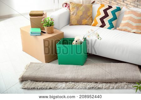 Sofa, carton boxes and interior items in room. Moving house concept