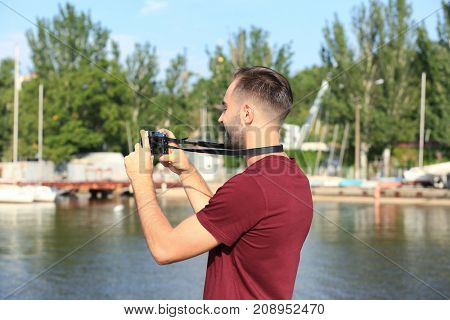 Handsome young tourist with camera standing on river bank