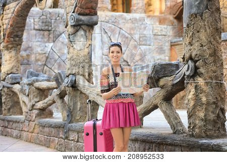 Beautiful young tourist with map and suitcase standing near ancient wooden fence