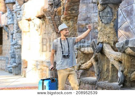 Handsome young tourist taking photo with mobile phone near ancient castle