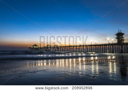 Surreal scenery as the sun sets below the horizon along Huntington Beach, casting a beautiful glow and peaceful landscape.