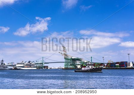 A tugboat motors across ports of call in Long Beach California in route to escort a freighter to the loading docks.