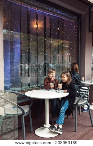Children having fun in outdoor cafe. Kids talking and drinking cocoa for the breakfast in the city street in autumn.