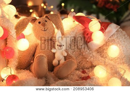 Christmas composition with baby toys and Santa Claus hat on plaid at home