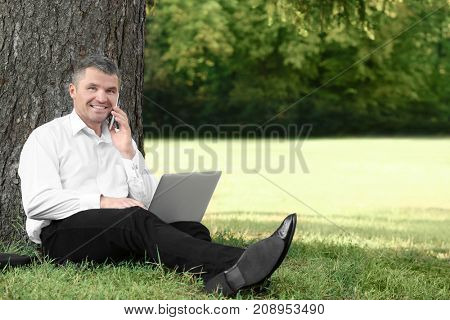 Elegant businessman sitting in park with laptop and talking on mobile phone