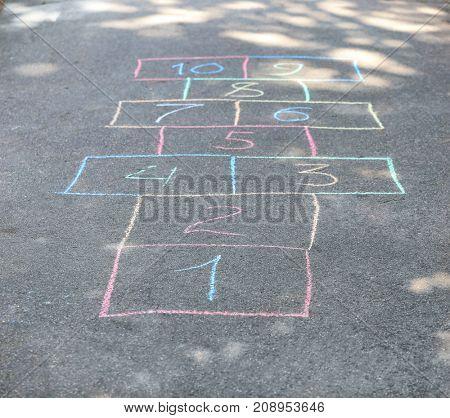 Hopscotch drawn with chalk on asphalt