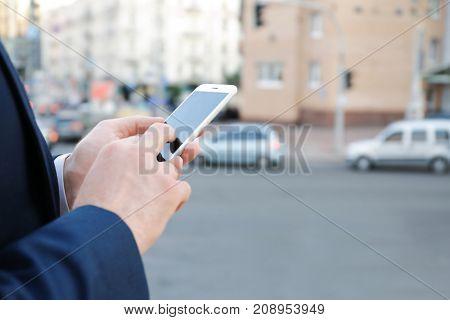 Elegant businessman using mobile phone outdoors, closeup