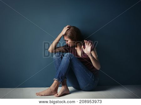 Battered young woman sitting near blue wall
