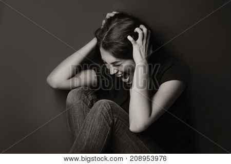 Battered young woman sitting near wall