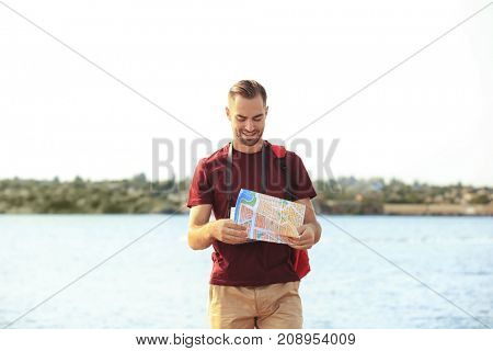 Handsome young tourist with map standing on river bank
