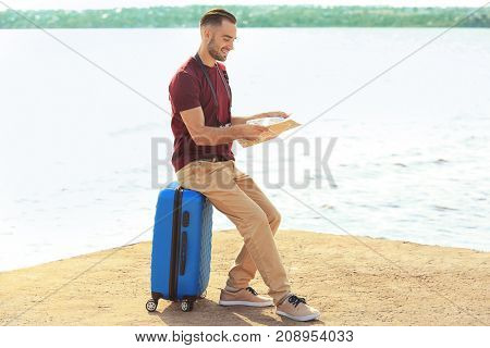 Handsome young tourist with map sitting on suitcase near river