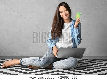 Young woman using laptop while holding credit card at home. Internet shopping concept