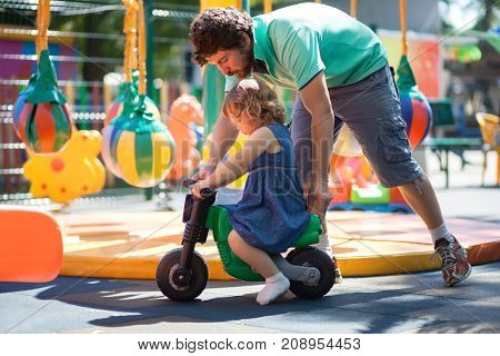 Father play with his toddler daughter riding her on a toy bike. Family leisure. Loving caring single father. Kid playing with parent indoors kindergarten.
