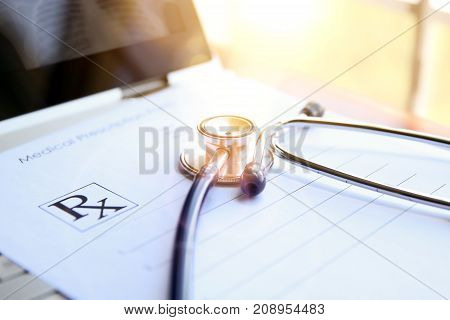 prescription laptop and phonendoscope at the doctor`s table