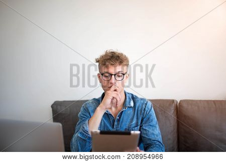Serious man freelance social media content writer working with digital tablet and laptop computer. Young hipster guy in glasses successful lifestyle writer using touch pad, sitting in modern interior