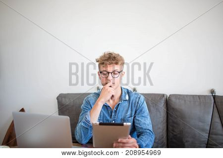 Male skilled professional business content writer thinking about news ideas using laptop computer and digital tablet. Young man successful developer sites working with modern touch pad and net-book