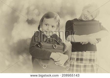 Adorable old-fashioned happy little 6 years old and 10 years old girls back to school concept. Preschooler and schoolgirl Sisters schoolkids. Horizontal old vintage retro monochrome black and white photo.