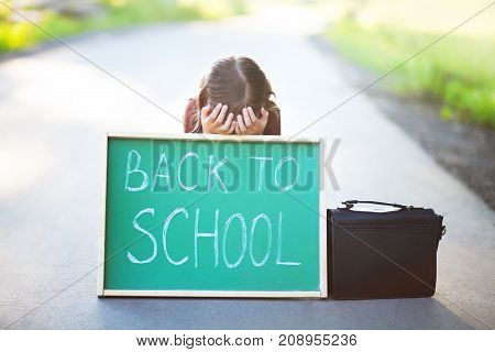 Depressed little girl hiding behind the chalkboard amd crying don't want back to school. Have promlems with schoolmates or teathers. Stressed outsider kid. Teathers pressure consept. Negative feelings fear of school.