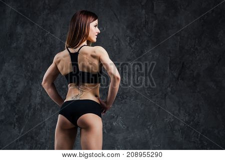 Dark contrast photo of back side of young beautiful fitness woman with beads of sweat which training in gym