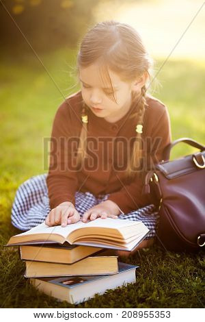 Adorable happy little preschooler girl with pigtails ready back to school reading textbooks outdoors school books manuals. Wearing school uniform. Warm september fall day. Smart clever intellegent little girl.
