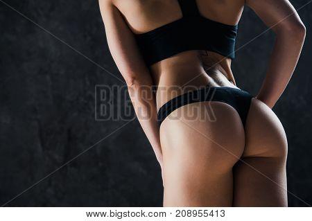 closeup woman beautiful buttocks over dark background.