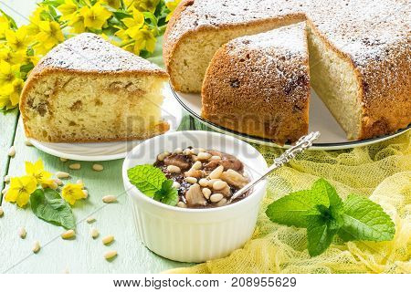 Delicious homemade pie with ricotta marshmallow and raisins banana dessert with chocolate marshmallow siberian pine nuts. Served in white dish on green wooden background with yellow gauze napkin