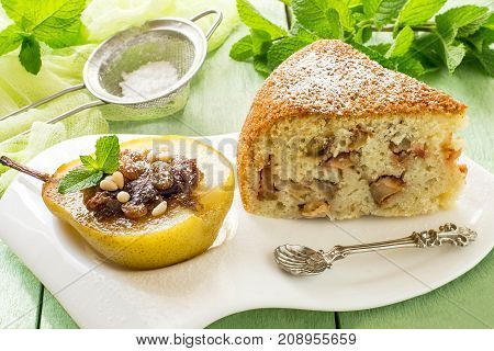 Sweet dessert: baked pear with raisins dates honey nuts spices and slice of delicious pie with apples on white plate sieve with powdered sugar mint on green wooden table with yellow gauze napkin
