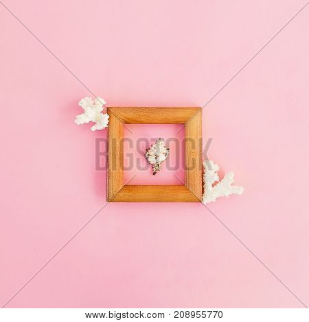 Wood frame, corals and seashells isolated on a pink background, flat lay, top view