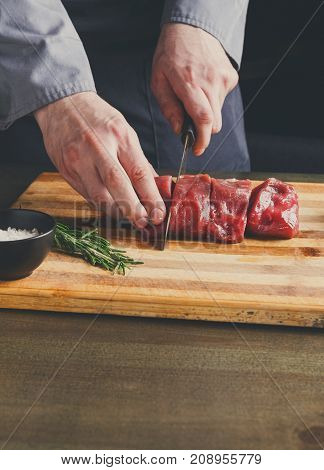 Male chef slicing filet mignon on wooden board at restaurant kitchen. Preparing fresh meat for cooking, seasoning with salt and rosemary. Modern cuisine backgroung with copy space, vertical