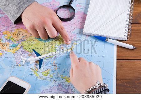 Couple planning airplane trip to Japan, point on map, taking notes in blank notebook, copy space