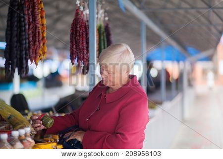Eldery woman at the bazaar buying food ingridients.