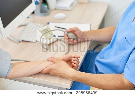 Closeup of doctor measuring blood pressure of female patient using automatic blood pressure monitor