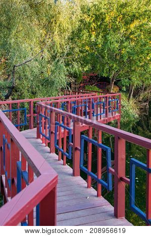 A red and blue zig-zag bridge crossing a calm pond in a park like setting in fall.