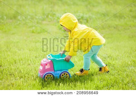 Adorable little girl plays with her new color toy car at the backyard. Cold summer or spring. Chlidren active play. Having fun outdoors.
