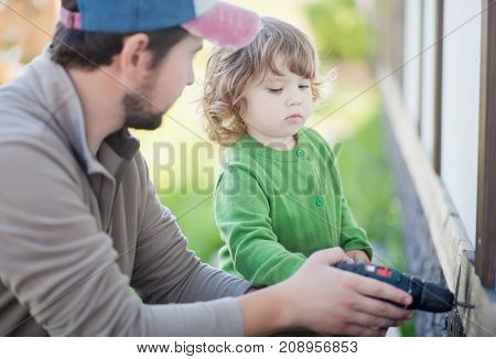 Father and his little daughter with drill outdoors. Family leisure spending time togetger.